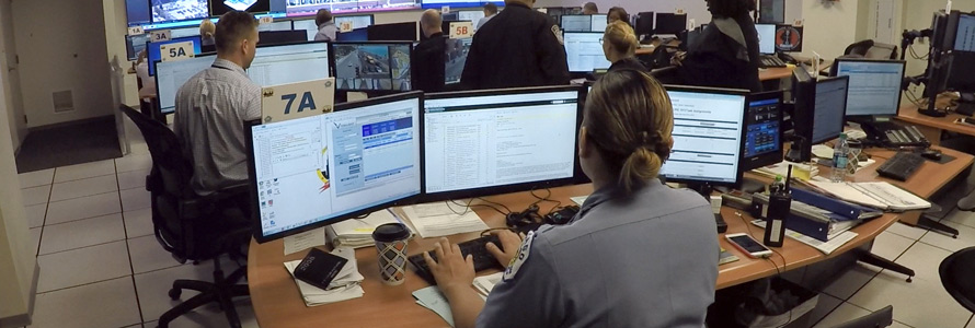 Emergency call ceneter with personel in front of three monitors