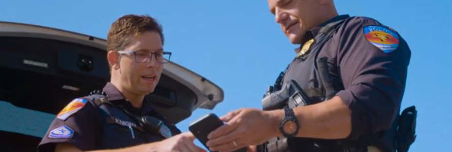 Two Town of Duck officers look at a smartphone