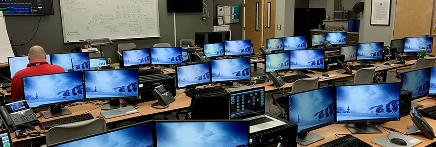 APCO_repost: A man sits surrounded by rows of monitors set up to serve as a mobile command center for Fulton County.