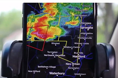Close up of a phone displaying storm maps in Connecticut