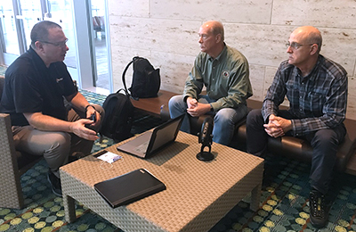 Brent Williams, Dr. Paul Zeeb, and Jack Rupp sit around a table which holds a laptop and a microphone.