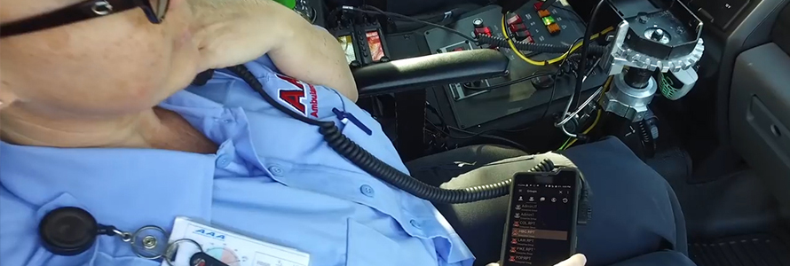 An emergency medical practitioner sits in an ambulance, speaking into a radio handset connected to a cell phone.