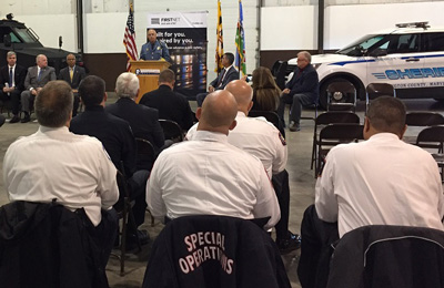 During an event marking one year of FirstNet in the State of Maryland, Sheriff Mullendore speaks at a podium in front of police vehicles