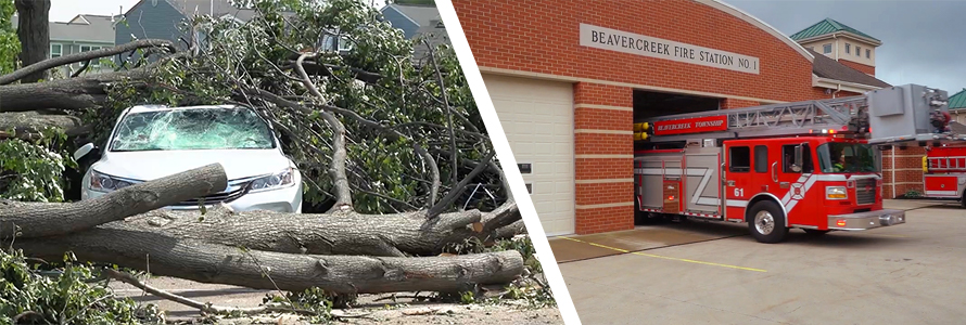 A car crushed by a fallen tree surrounded by branches and tree trunks; a Beavercreek Township fire truck leaves the fire station.