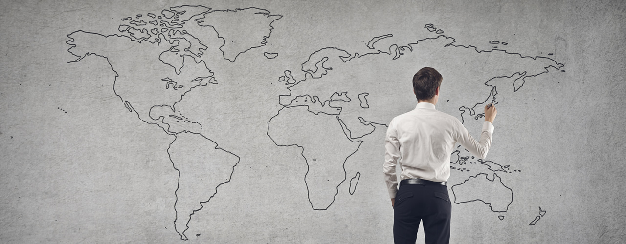 A man stands infront of a map of the world