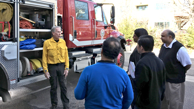 Firefighters talk to a group in front of an attack engine at the FirstNet Lab.