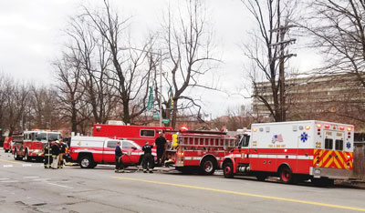 Two firetrucks, an ambulance, and other emergency vehicles gather at an incident by the side of the road