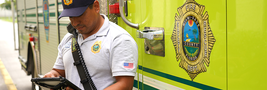 Fire fighter standing in front of a fire apparatus wearing a radio while typing on a mobile device.
