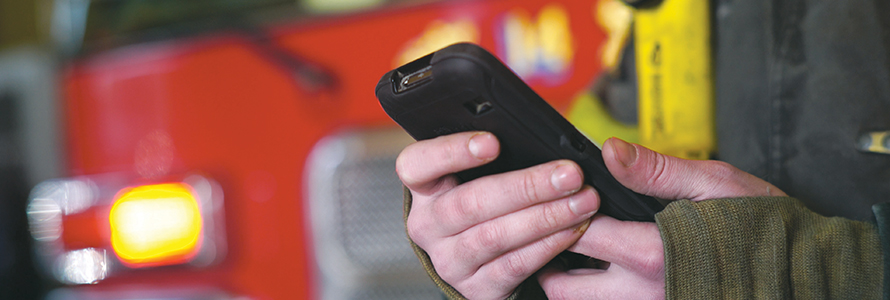 Firefighter holds FirstNet-enabled smartphone