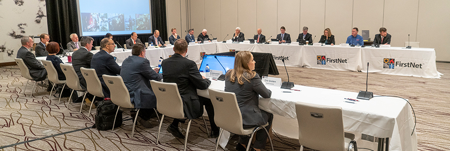Numerous FirstNet board members sit a tables facing each other during a meeting reviewing a presentation