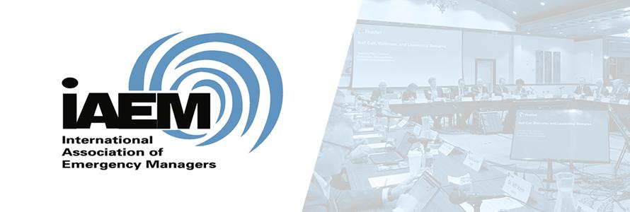 International Association of Emergency Managers (IAEM) logo and image of IAEM representatives making a presentation at a FirstNet Authority Board Meeting.