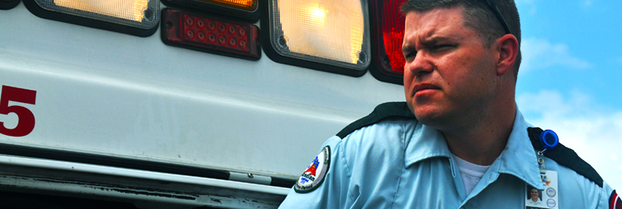 Emergency medical services professional stands in front of ambulance