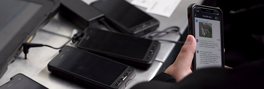 A Washington County law enforcement officer holds a FirstNet enabled device near several other devices being charged