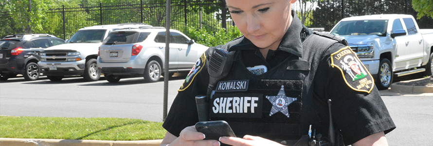 A female Loudon County sheriff in uniform looks down at a phone