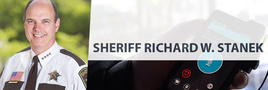On left, headshot of Sheriff Richard Stanek in uniform, on right, a hand holds a FirstNet device with an app on it