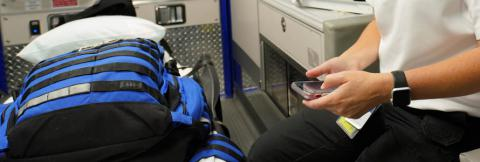First responder in an ambulance holding a cell phone