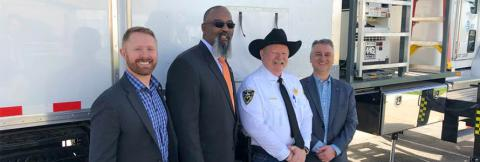 Sheriff Mike Hollinshead of Elmore County, Harry Markley from the FirstNet Authority and others stand in front of a FirstNet SatCOLT