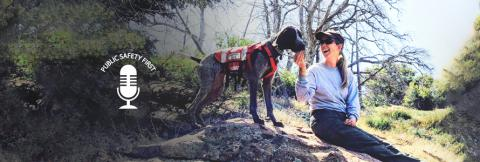 First responder in the woods with her search and rescue dog