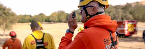 Santa Clara responder speaks into a smartphone while in the field