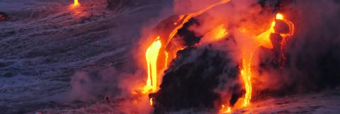 Orange lava flows down the side of a volcano