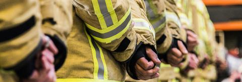 Firefighters stand in a line with their hands clasped behind their backs.