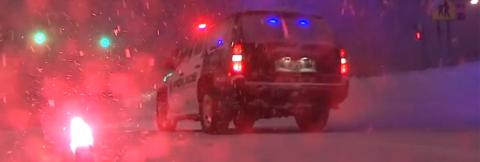 A police SUV with lights on and lit flare sit in a snowstorm at night.