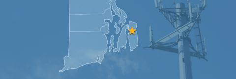 The state of Rhode Island, with outlined county borders and a star locating Tiverton, Rhode Island; a cell tower.