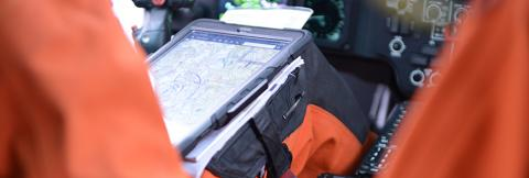 U.S. Coast Guard pilot using tablet, seated in cockpit