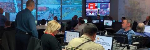 Emergency managers monitor computers during Kansas City Chiefs Super Bowl Parade; large screen projects live camera streams in emergency operations center in Kansas City, Missouri.