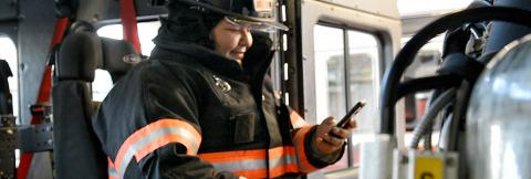 Firefighter using smartphone inside firetruck
