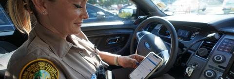 A female police officer sits in a patrol car looking at a cell phone.
