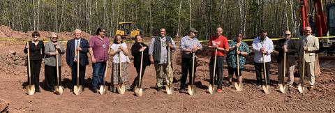 Thirteen people stand with gold shovels, ready to break ground on a cell tower at Red Cliff Reservation