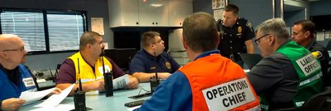 Emergency management and public safety professionals sit around a conference table in discussion.